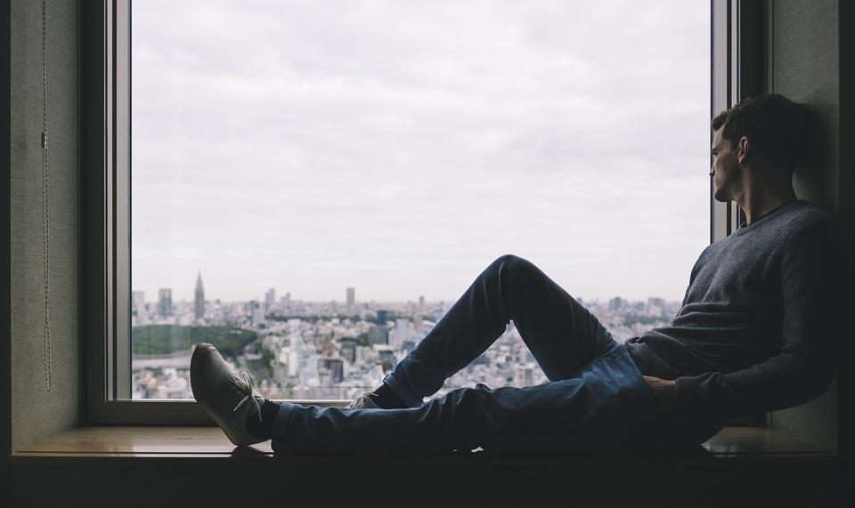 muž pozerá z okna