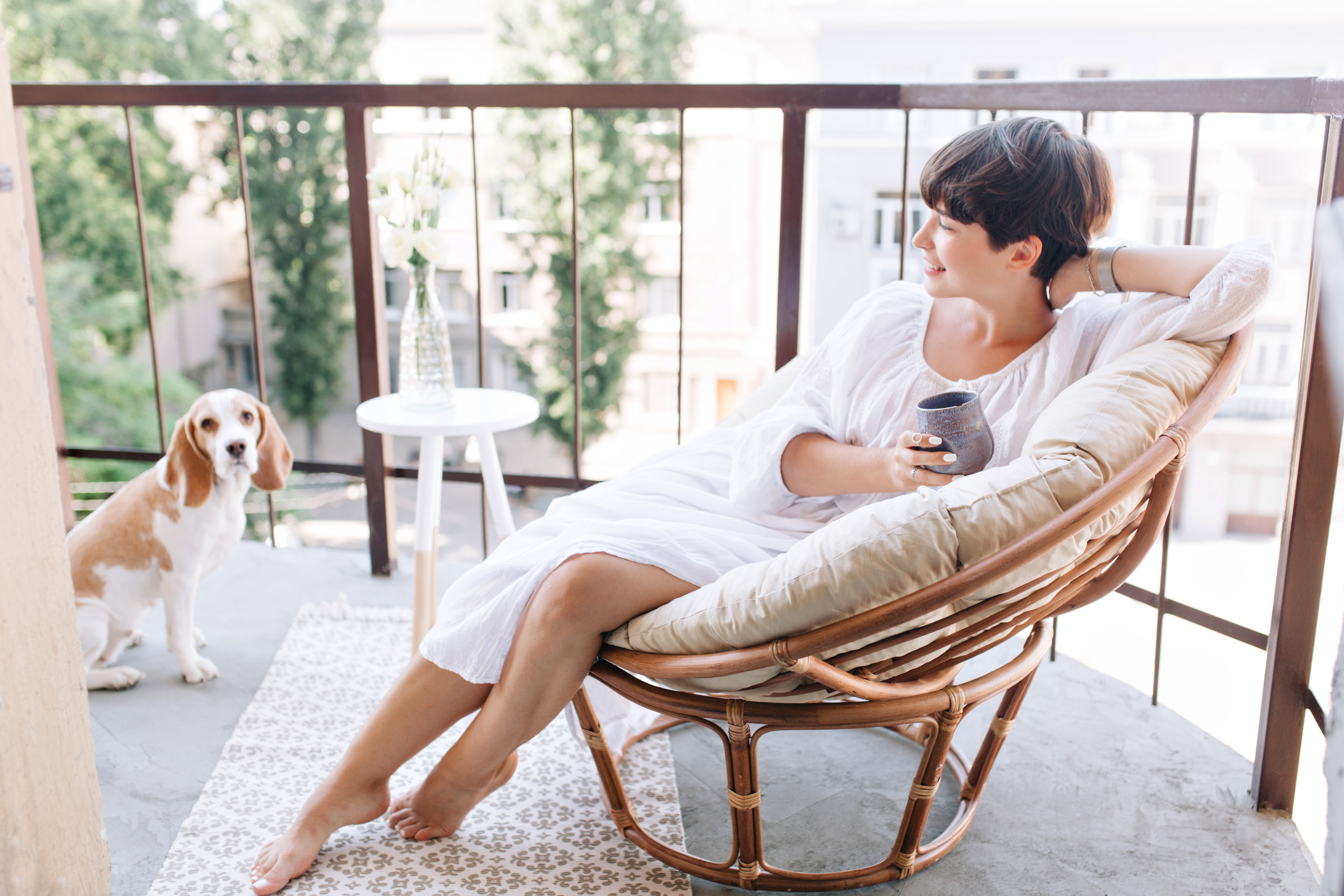 relaxed-barefooted-girl-white-dress-sitting-chair-balcony-holding-cup-tea (1)
